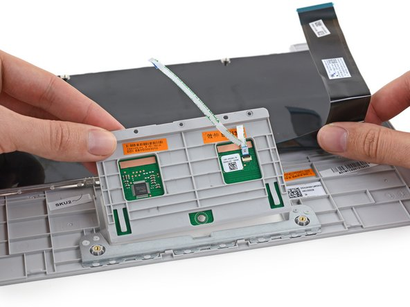 Keyboard and trackpad ribbon cables connect the upper case to the motherboard, with plenty of slack to flip the upper case over and safely disconnect the ZIF connectors from the motherboard.