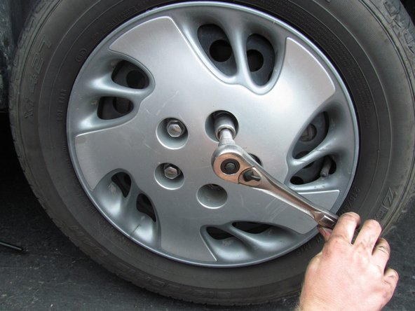 Loosen the plastic lug nuts, located on the hub-cap, with a 19mm socket.