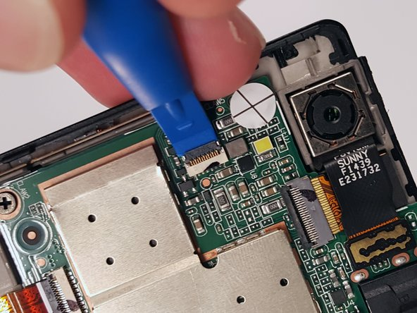 Remove the the ribbon cable located under the camera. Take a plastic opening tool and gently lift the black flap on the ribbon cable connection.