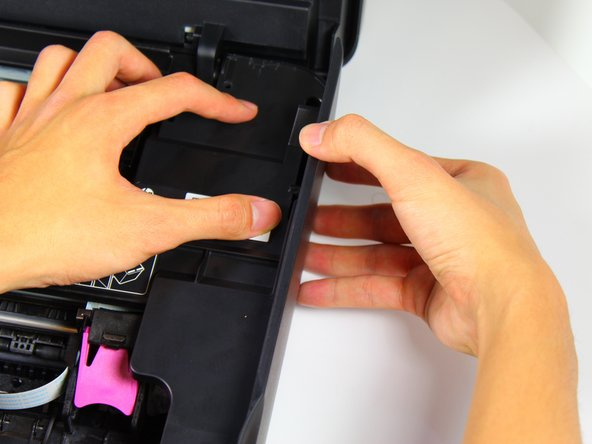 Detach the right-side panel by applying downward pressure on the internal protective cover with one hand and pulling the right-side cover with the other.
