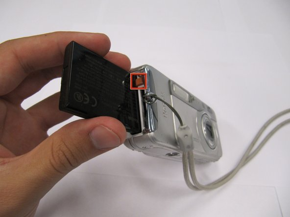 Slide the orange latch sideways to eject the battery.