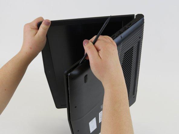 ラップトップ本体を立てかけて、スパッジャーもしくはクレジットカードでボトムカバーをこじ開けます。デバイスをしっかりと掴めるように、ラップトップを若干開いて作業するとし易くなります。