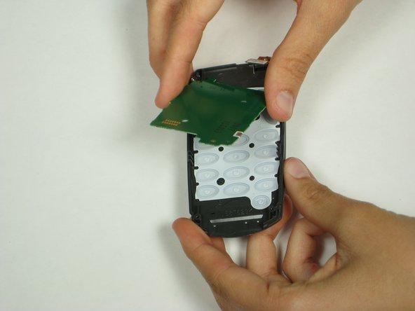 Une fois la carte logique retirée, soulevez le capteur vert du clavier depuis la plaque avant.