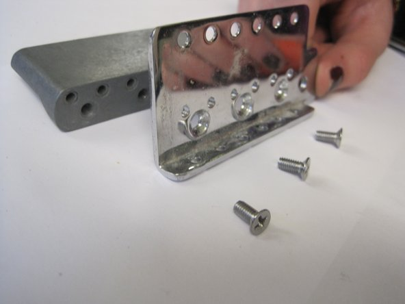 Unscrew bridge from the tremolo block.