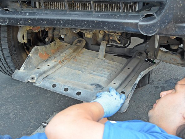 Do not lie directly beneath the skid plate when removing the it. The skid plate or any debris trapped inside may fall on you.