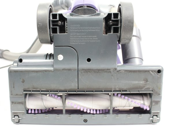 Using the metal spudger, pry the two small wheels located at the two bottom corners of the vacuum to remove them.
