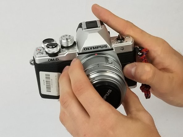 While holding down the button specified in step 1, begin turning the inner most ring, specified in step 2, counterclockwise until the camera lens becomes free from the camera body.