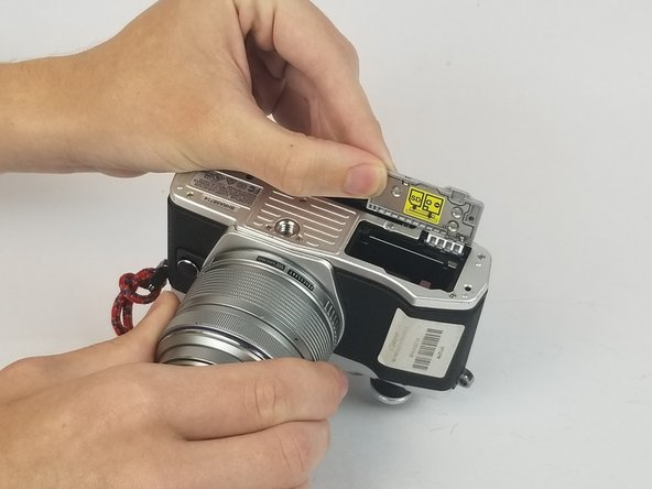 Grab the SD card door and remove it by pulling it away from the body of the camera.