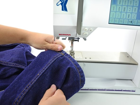 Image 2/3: Make sure the pant leg is around the arm of the sewing machine, so that you don't sew the pant leg shut. There should only be the two layers of the fold between the presser foot and the sewing machine arm.