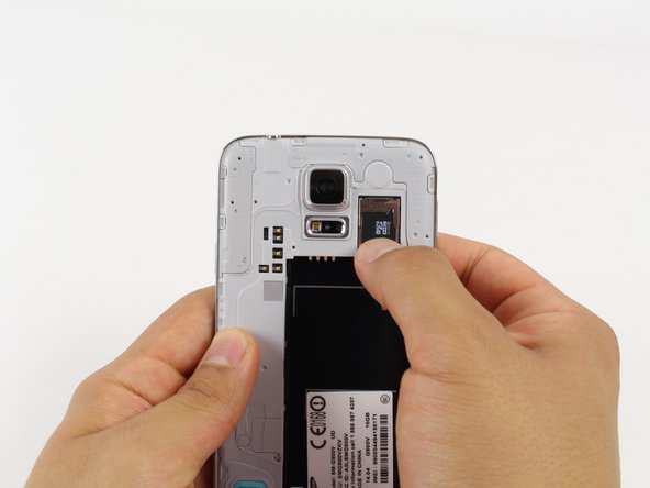 Gently slide out the SD card using your fingernail or a plastic opening tool.