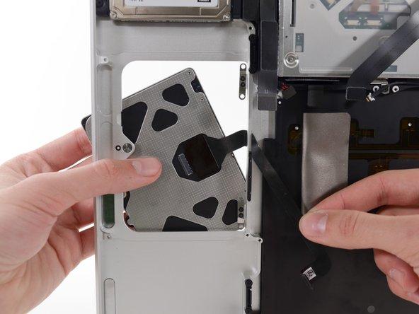 Sobald das Trackpad aus dem oberen Gehäuseteil befreit ist, führe das Flachbandkabel durch den schlitzförmigen Ausschnitt im oberen Gehäuse.