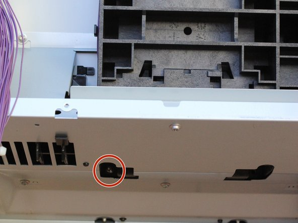 Tilt the printer forward and remove the Phillips screw with a lock-washer from the bottom area of the printer.