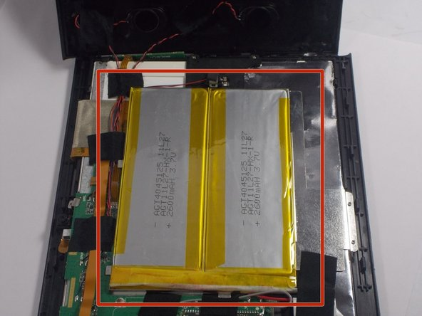 Upon opening  the device the battery is clearly visible, on the side of the logic board. It is a silver rectangular shaped battery with yellow tape around the border and is attached to a silver metal plate, which holds the battery in place.