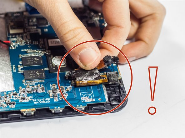 Grasp the camera unit with tweezers or fingers, and pull firmly to remove it from the adhesive holding it to the motherboard.