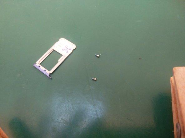 Vergeet op het einde niet de 2 schroeven onderaan er terug in te schroeven, de sim tray terug te plaatsen en eventuele covers.
