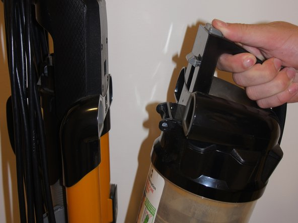 Press the grey dust cup release button and gently pull the dust cup towards you.