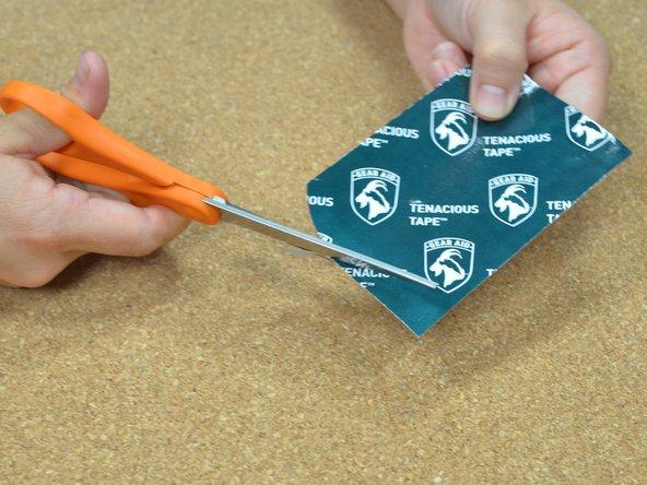 Ritagliare un ovale di nastro adesivo per tessuti abbastanza grande da coprire lo strappo.