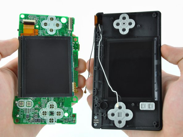 Image 2/2: Pull the motherboard away from the DS Lite to separate the upper LCD ribbon cable from its socket on the motherboard.