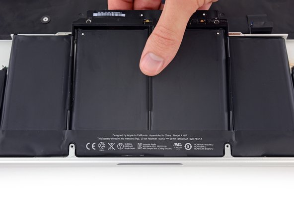 Lift the battery with the plastic frame and slide it back toward the MacBook Pro's hinge until it clears the screw posts holding it to the upper case.