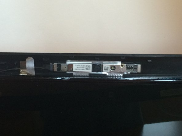 Carefully pull the top of the monitor cover off with bottom still attached, and view the webcam attached by a wire.