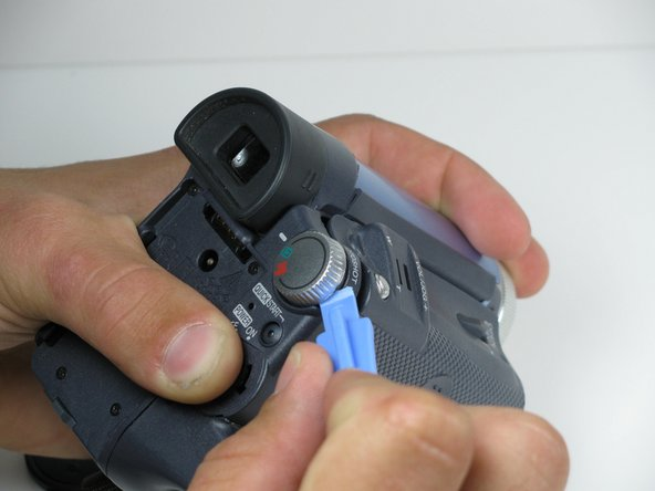 Using a plastic opening tool, remove the record/playback and record/power control knobs from the camcorder.