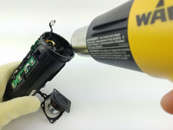 Gently heat adhesive located at tip of powerchip to melt the plastic fastening the battery to the housing. Be careful not to melt the plastic housing during heating.
