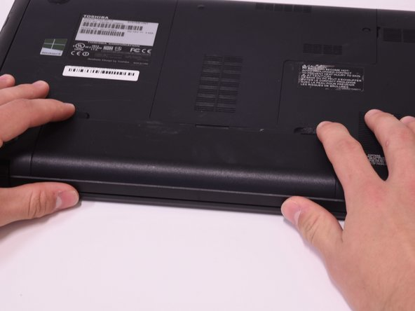 Use two fingers to pull the ridged lock tabs on the bottom of the computer toward the edges. This will unlock the battery.