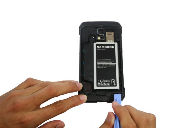 Insert a fingernail or plastic opening tool into the recess in the bottom right corner of the battery and lift upward.
