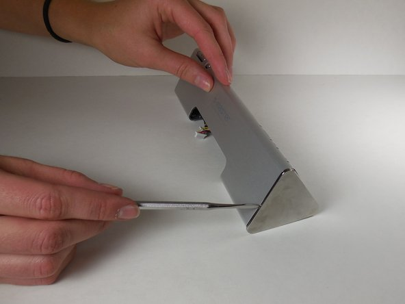 Using the metal spudger, loosen the metal cap at the end of the speaker.