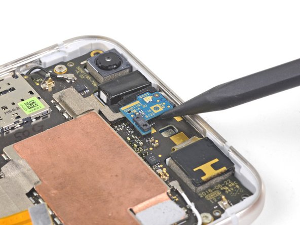 Carefully slide the point of a spudger under the proximity sensor board and pry up to disconnect it.