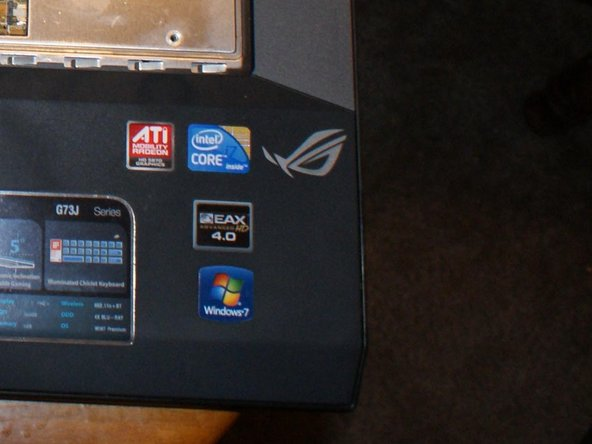 See that thin, black seam to the right of the Asus ROG logo?  That's the seam between the top cover and the bottom enclosure.  Use a small flathead screwdriver or plastic spudger and gently pry the top cover up to release the retention tabs.  Do this all the way around the seam.