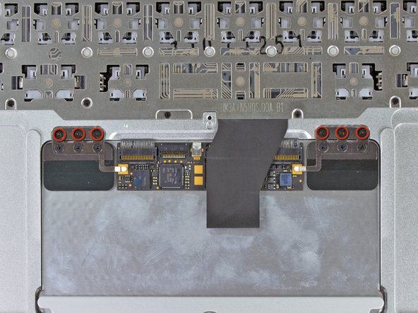 Remove the six 1.5 mm Phillips #00 screws that secure the trackpad assembly to the upper case.