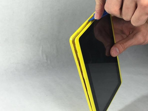Image 2/2: Start by edging the corner of the opening tool into the edge of the device and work your way from there until the back cover is removed.