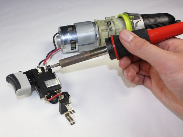 To separate the trigger assembly from the motor, use a soldering iron to melt the solder and pull gently on the red and black wires from the trigger.