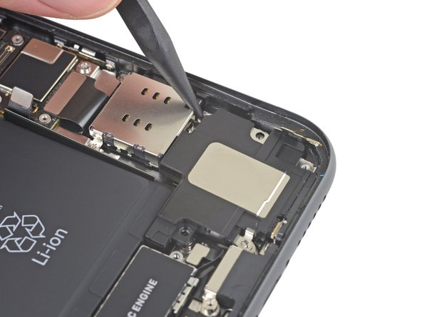 Insert a spudger under the top edge of the speaker, near the edge of the iPhone's case.