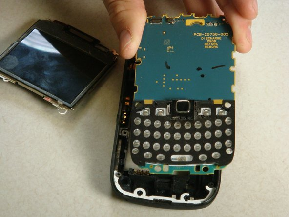 Now the motherboard will lift up out of the plastic backing of the phone.
