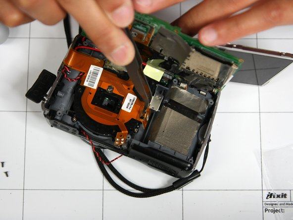 Using tweezers, gently remove orange circuit from lens. This step is tricky as the orange circuit is very securely placed in the lens.