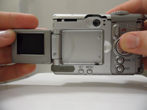 Image 1/2: Remove the rear cover by pulling it straight away from the body of the camera.