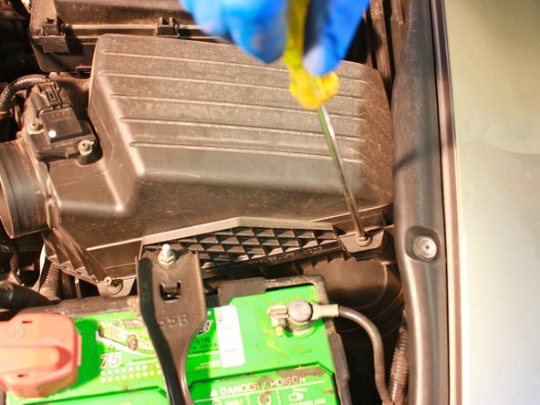 Image 3/3: Using a Long Philips Screwdriver or a Long 5/16 Hex Driver, remove the four screws holding down the air filter housing cap.