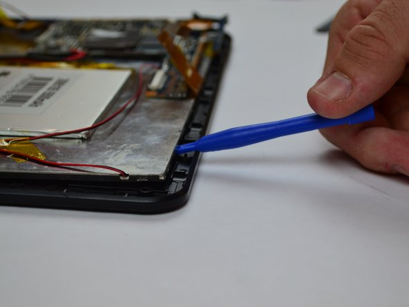 Begin lifting the display screen out of its housing with a plastic prying tool, sliding it around the perimeter of the screen.