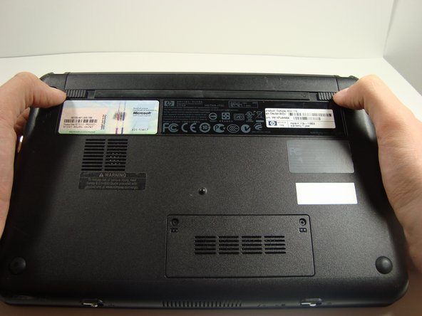 Find the battery and the battery tabs located on the bottom of the Compaq Mini.
