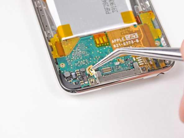 Image 2/2: Use a pair of tweezers to lift the Phillips screw out of the logic board.