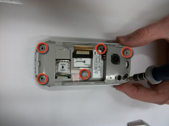Using the T5 or T6 screwdriver, remove the six screws from the back of the phone, as shown in the first image.