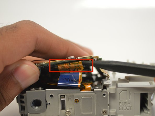 Use the spudger to remove the the ribbon cable attached to the motherboard. Be sure to alternate both sides of ribbon cable to evenly remove.