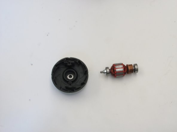 Image 2/2: The fan can be removed from the motor by unscrewing the bolt using a socket wrench. The bolt is inside the fan.