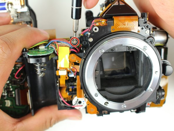 Remove one 5 mm J000 screw from the top right of the camera.