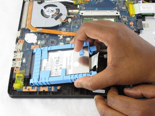 Using the ribbon beneath the hard drive lift it upwards and pull the hard drive out.