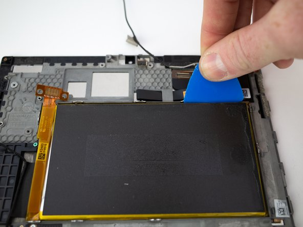 Slide a few opening picks between the battery and the raised metal edge.