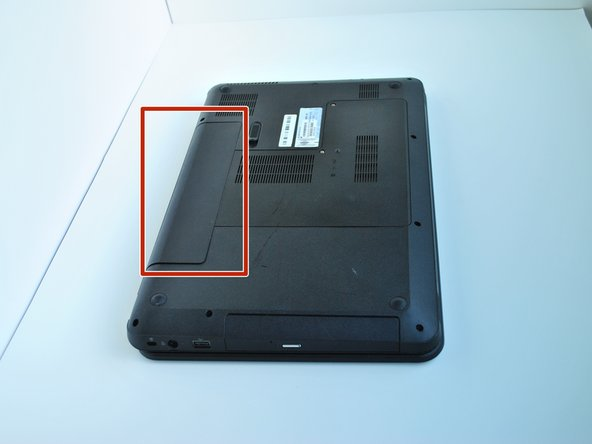 Flip the computer so that the bottom side is facing up, and locate the battery above the screen hinges.