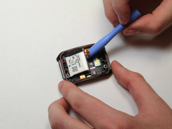 Image 1/1: Using the plastic opening tool, gently pry the battery up.